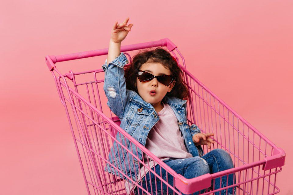 funny-child-sunglasses-sitting-shopping-cart-studio-shot-happy-little-girl-denim-jacket-960x640.jpg
